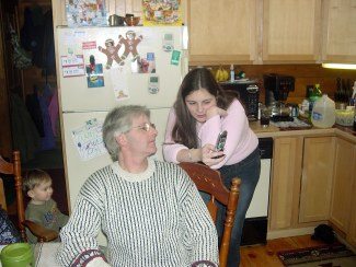 Uncle Chris shows Kayleigh the features of her new cell phone....